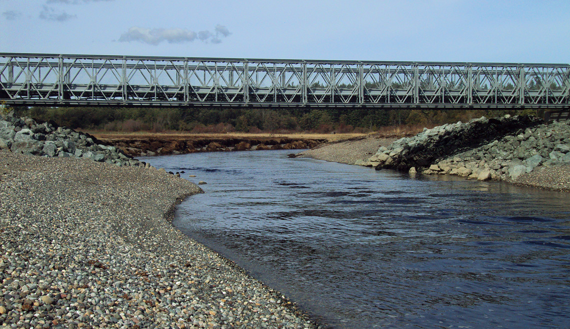 An incoming tide flowing beneath the bridged outlet channel opening at the Crescent Harbor Salt Marsh.